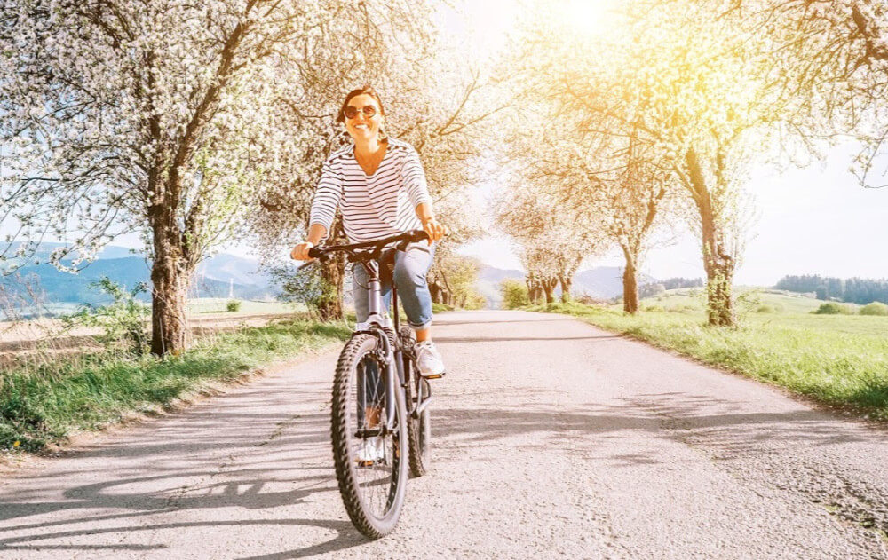 A woman rides a bike on a path with blooming trees